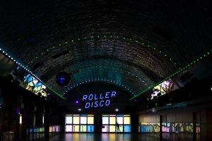 image of the entrance to a roller disco arena with a neon roller disco sign